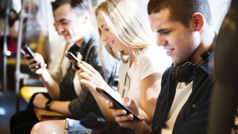Junge Erwachsene nutzen Smartphone in U-Bahn