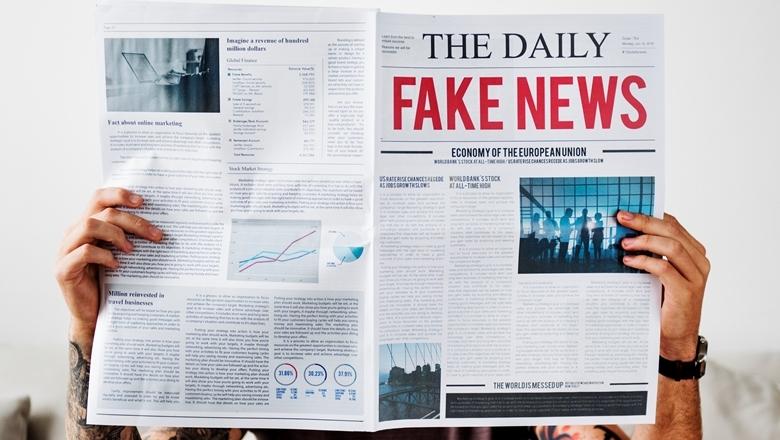 """Mann hält Zeitung hoch mit Überschrift """"Fake News"""""""