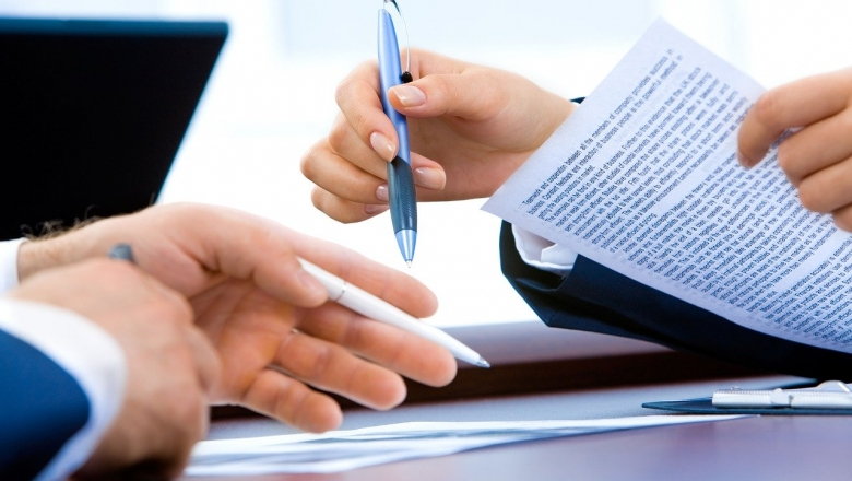 Zwei Personen besprechen einen Vertrag (Foto: Aymanejed)