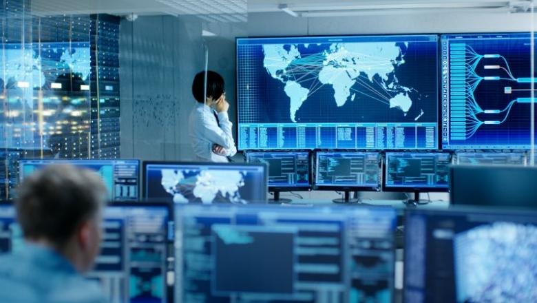 Foto von einem Raum voller Bildschirme, auf denen globale Logistikrouten angezeigt werden