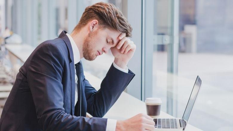 Mann in Anzug vor Laptop mit pessimistischer Miene