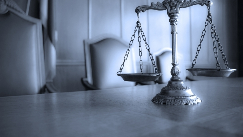 Foto mit einer Waage im Vordergrund, Gerichtssaal im Hintergrund