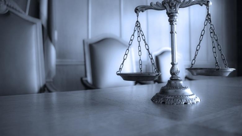 Foto mit einer Waage im Vordergrund, Gerichtssaal im Hintergrund (Foto: Shutterstock)