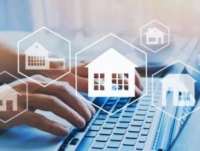 Immobilien-Icons im Vordergrund, zwei Hände auf einer Computertastatur im Hintergrund