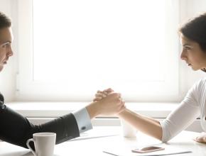 Armdrücken zwischen Mann und Frau in Business Kleidung
