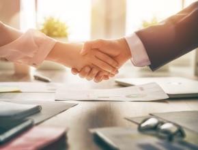 Mann und Frau in Business Kleidung schütteln sich die Hand