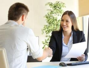 Mann und Frau bei Jobinterview schütteln Hände